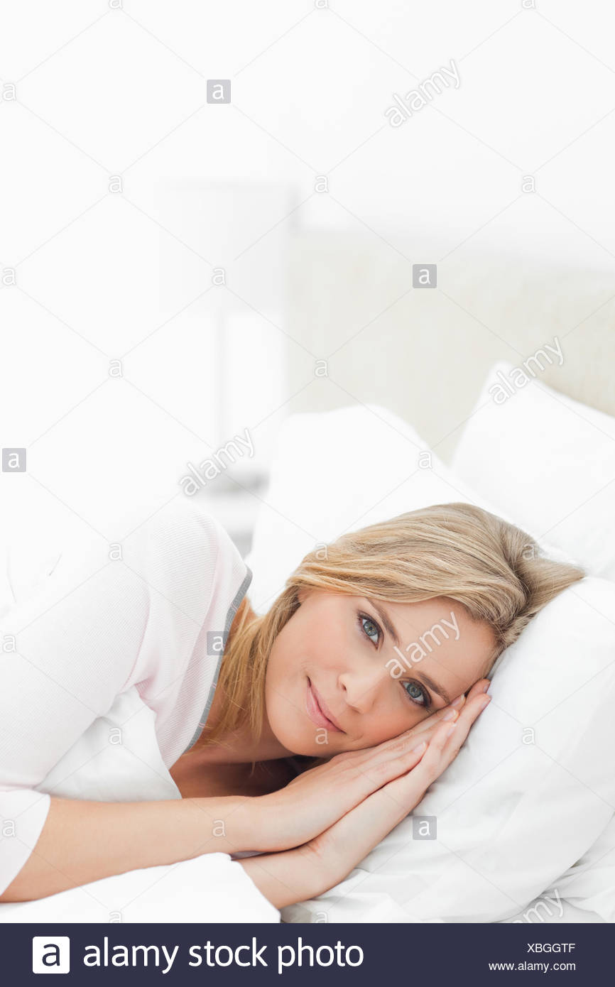 Woman Resting In Bed Eyes Open And Hands Placed Beside