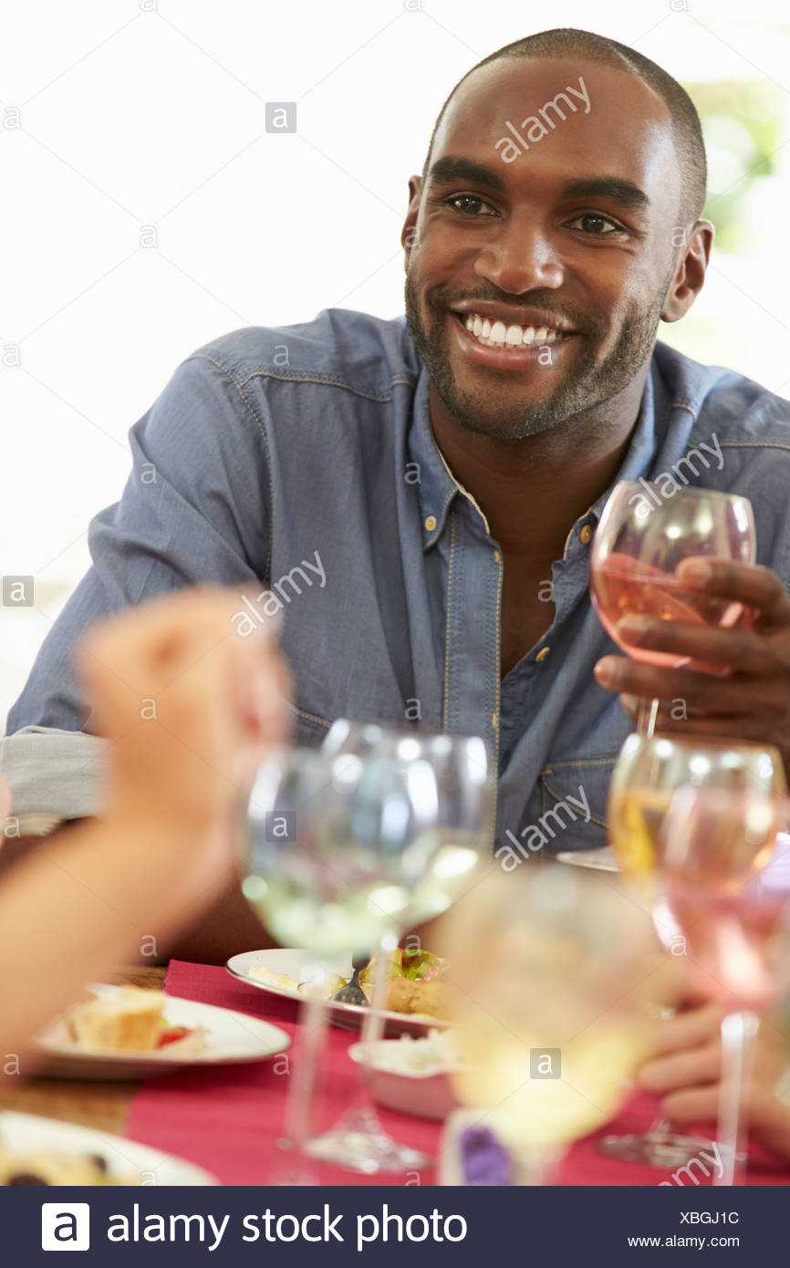 Young Man Relaxing At Dinner Party - Stock Image