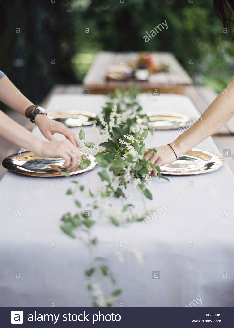 Two people leaning over a table laid outside with a white cloth and a central foliage table decoration - Stock Image