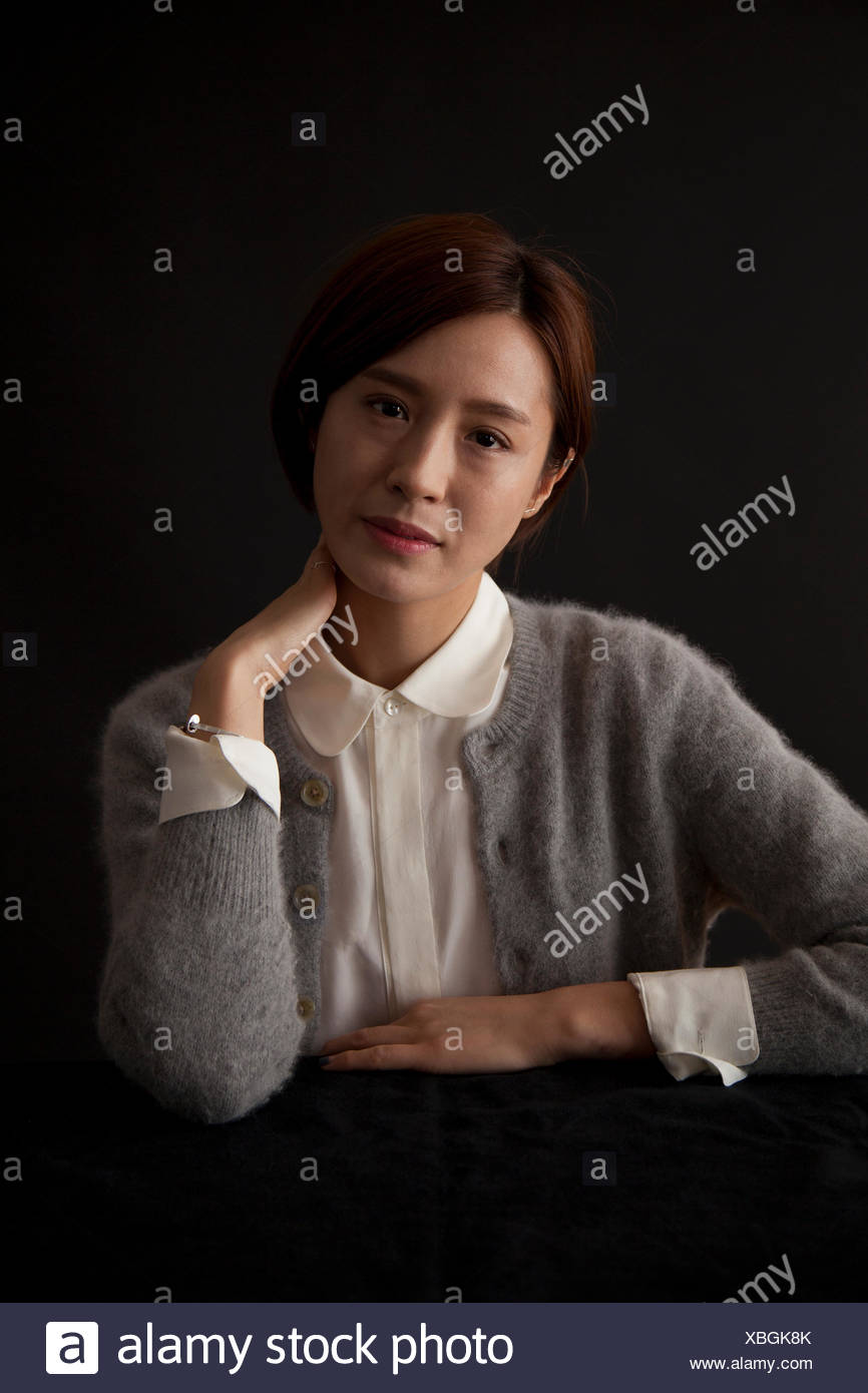 Portrait of woman sitting at table - Stock Image