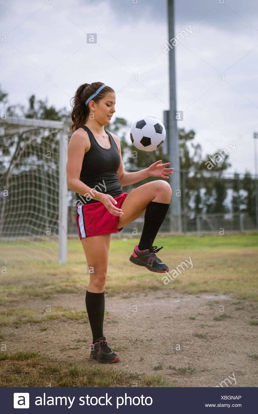 Soccer player bouncing ball on knee in field - Stock Image