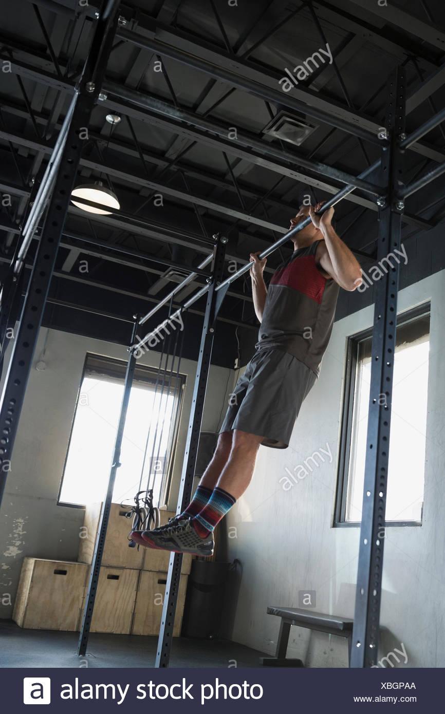 Man doing chin-ups at gym - Stock Image