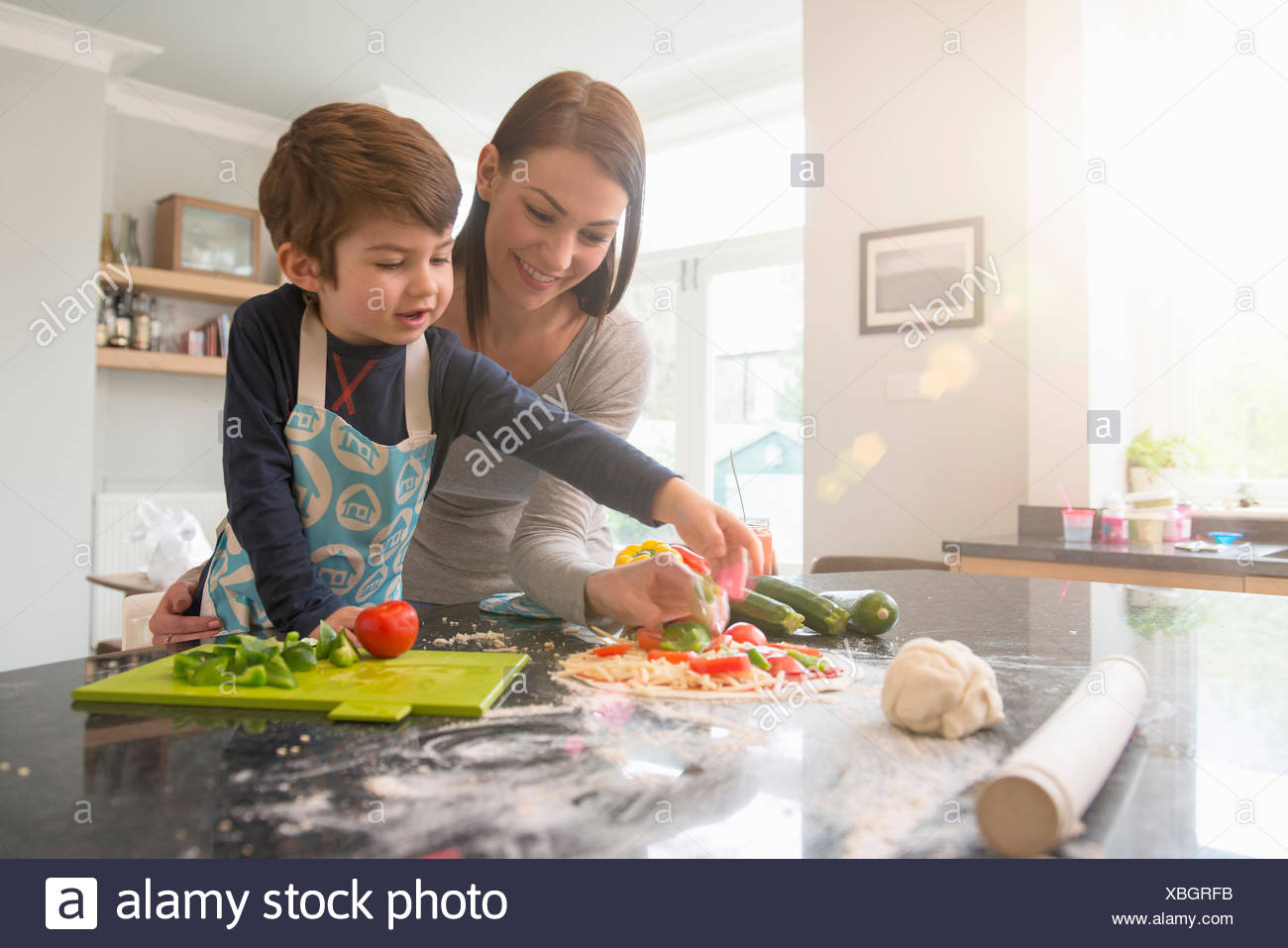 Mother and son preparing pizza together in kitchen - Stock Image