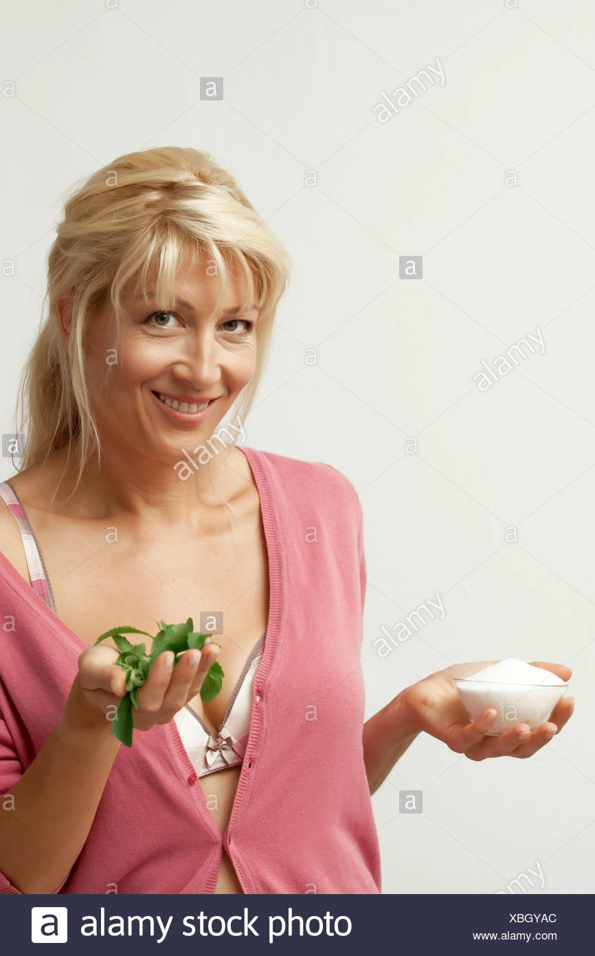 Mature woman holding stevia and sugar substitute, close up - Stock Image