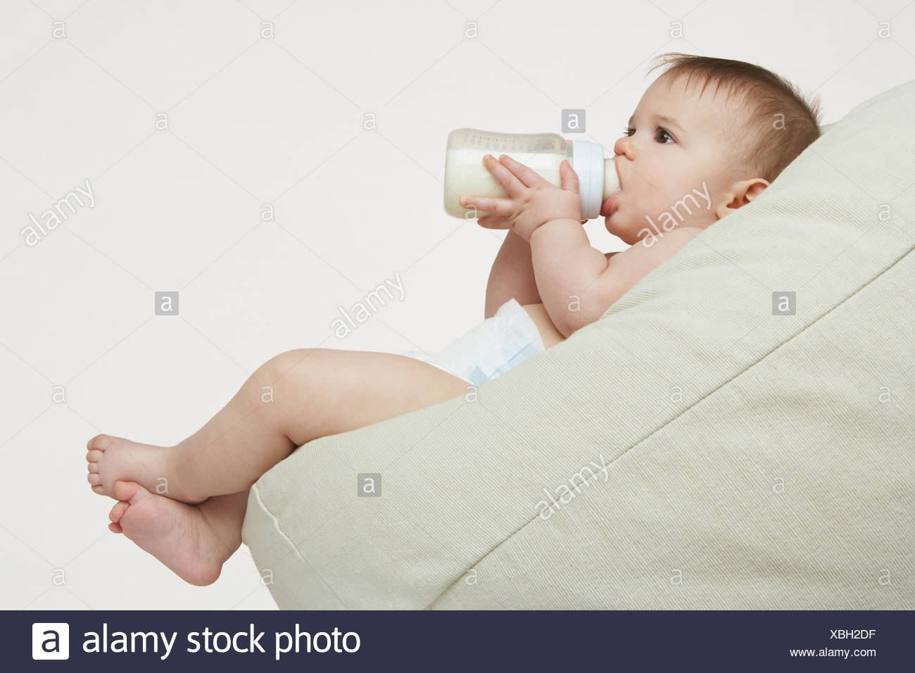 A baby with a bottle - Stock Image