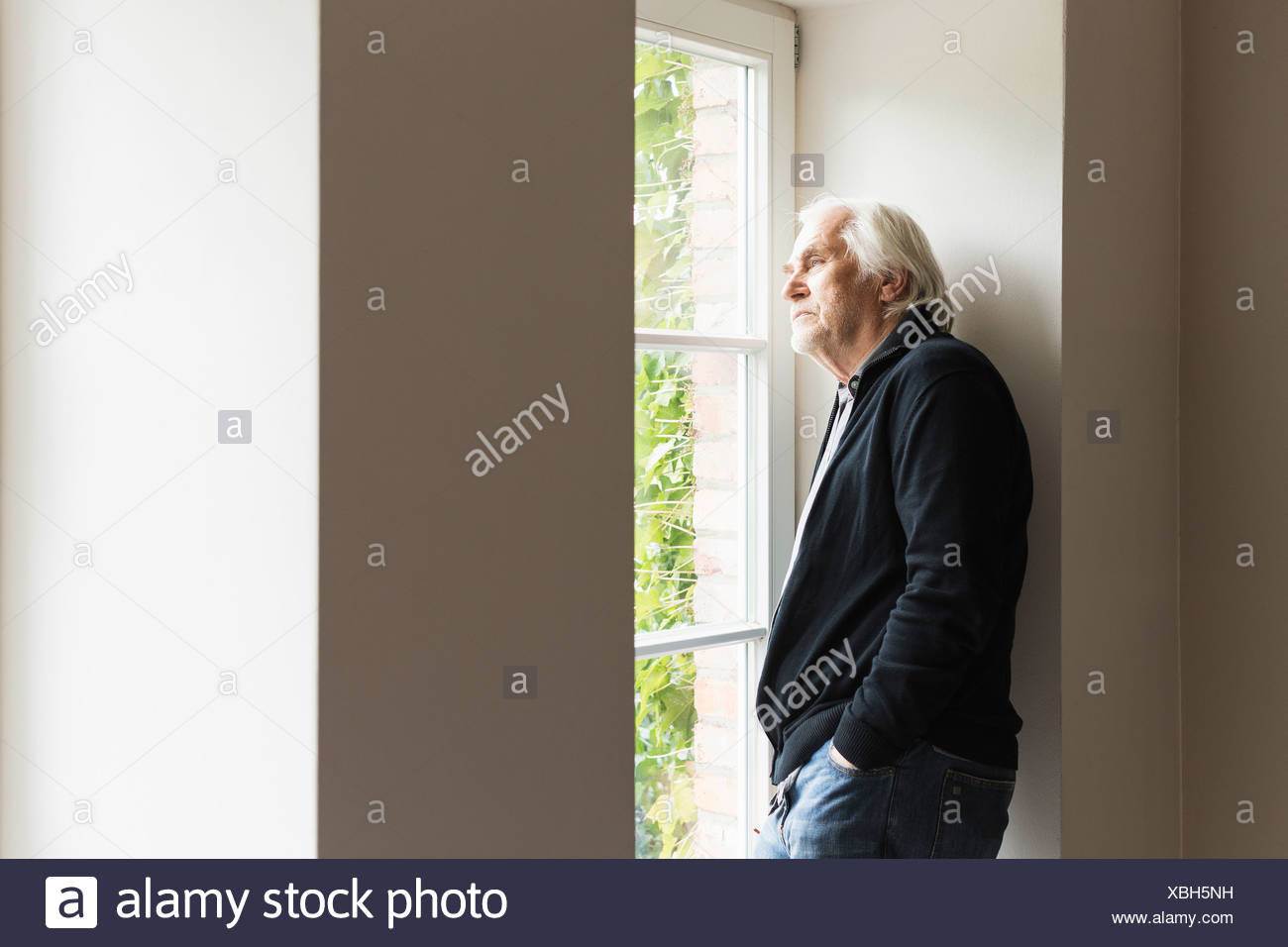 Portrait of senior man looking out of window - Stock Image