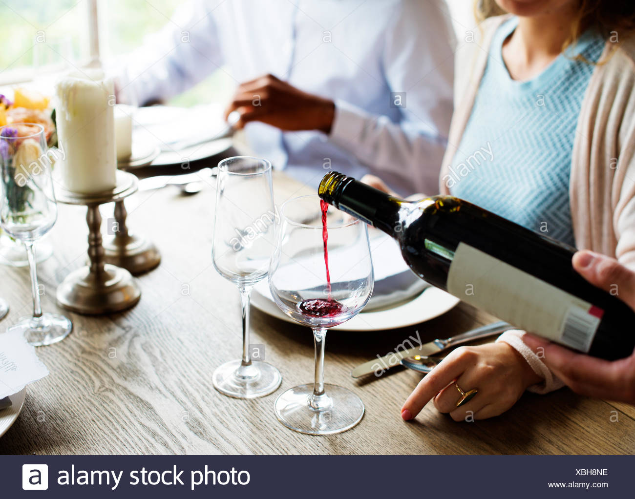 Waiter Poring Serving Red Wine to Customers in a Restaurant - Stock Image