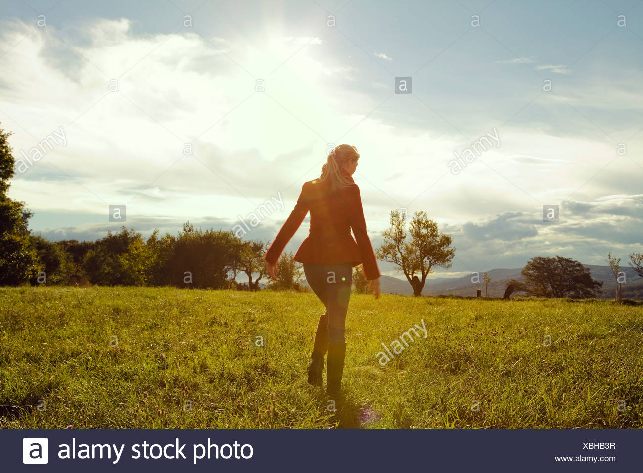 Young woman in field walking away - Stock Image