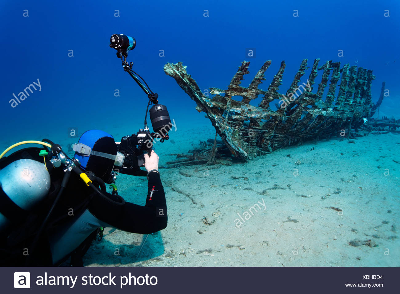 Underwater photographer taking photo of a wooden ship wreck, Makadi Bay, Hurghada, Egypt, Red Sea, Africa - Stock Image
