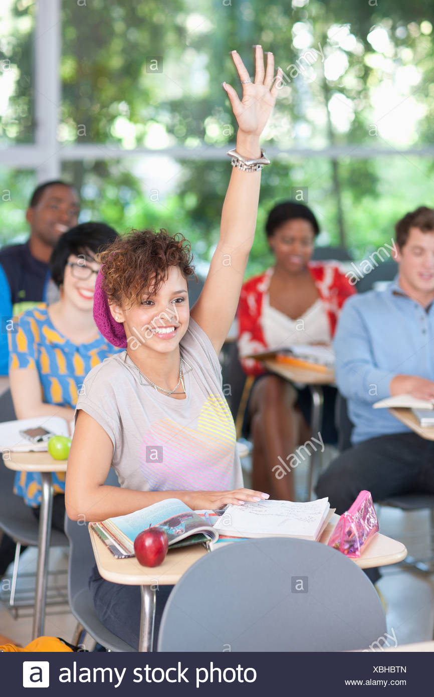 Student raising her hand in class - Stock Image