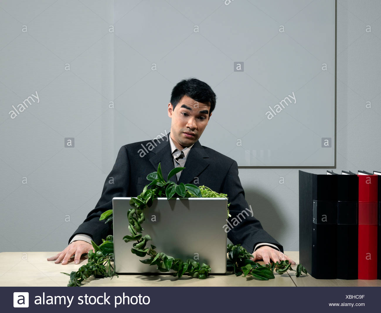 Man by desk beeing attacked by plants Stock Photo