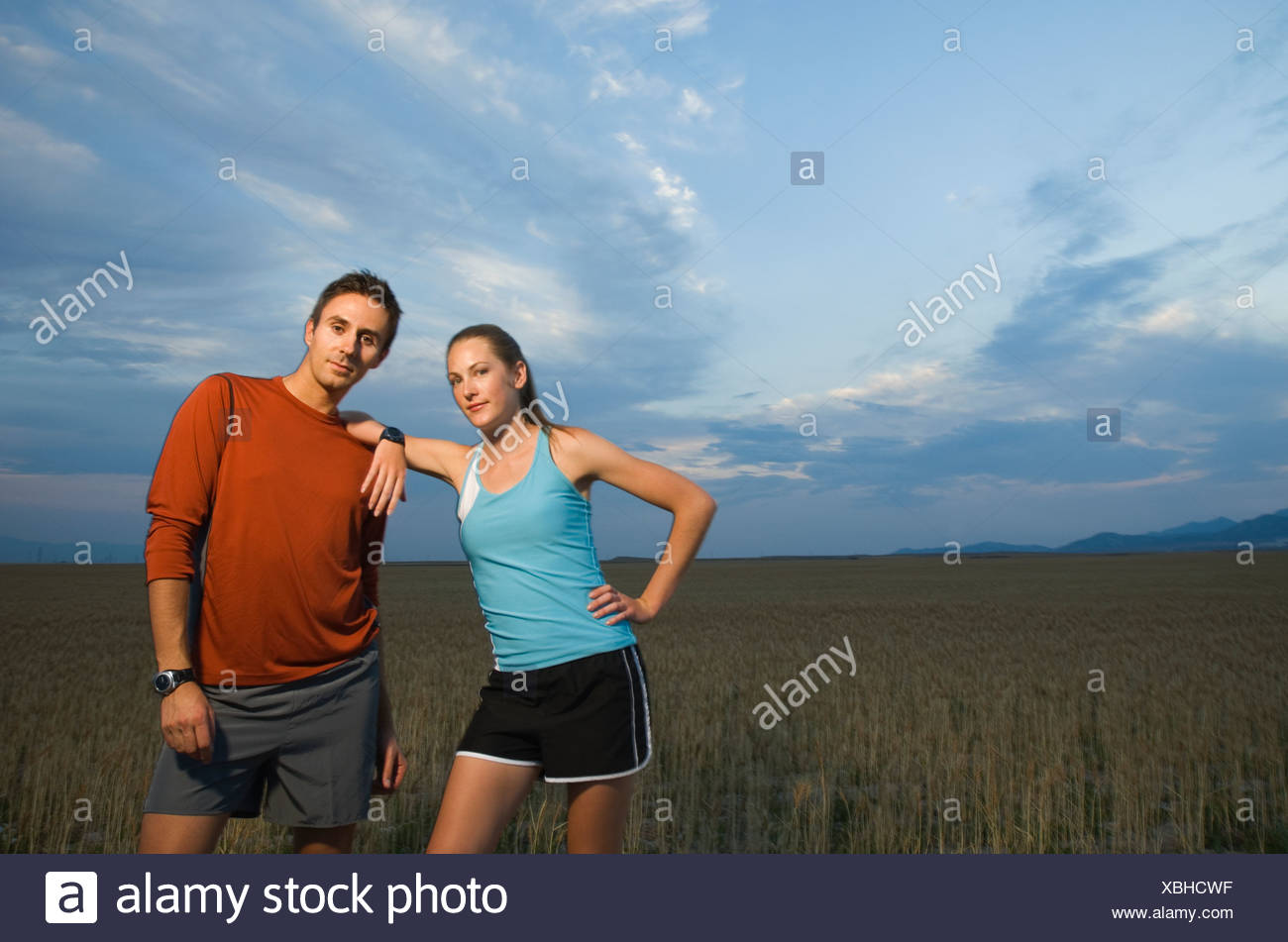 Couple in athletic gear next to field - Stock Image
