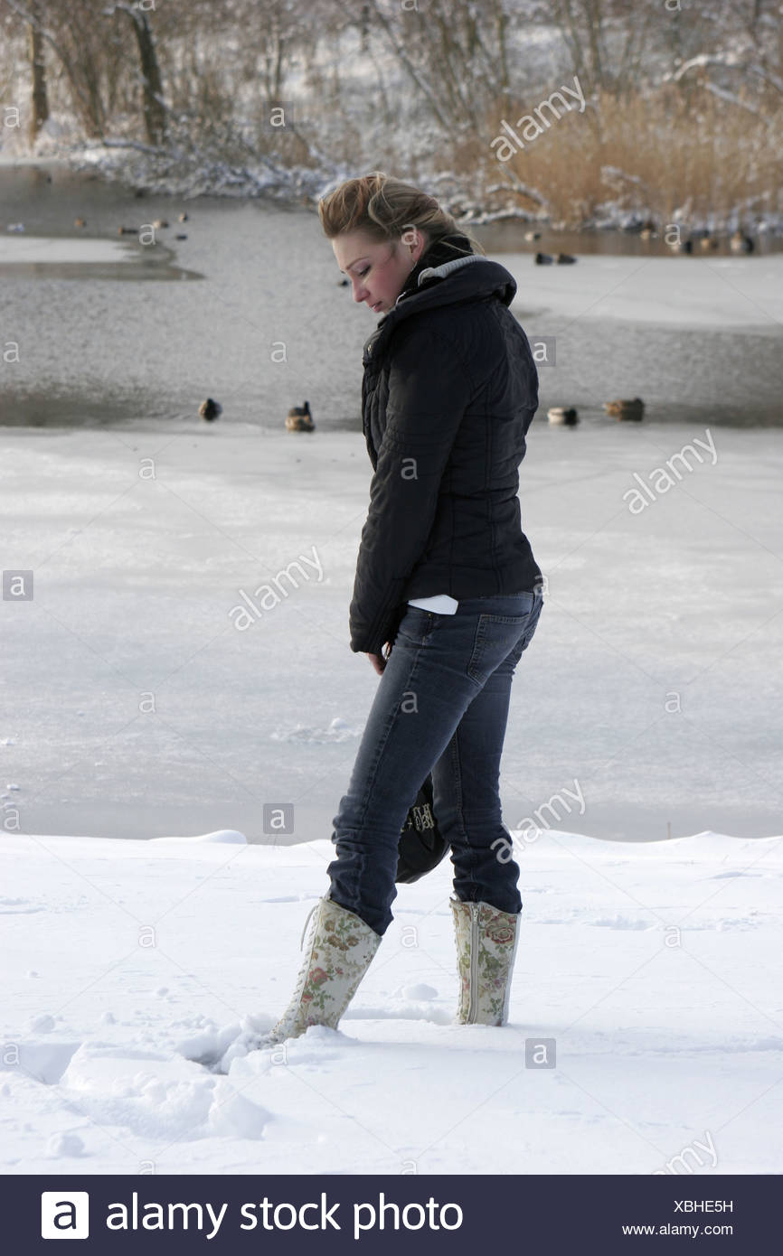 Depressed teen outside in winter snow park - Stock Image