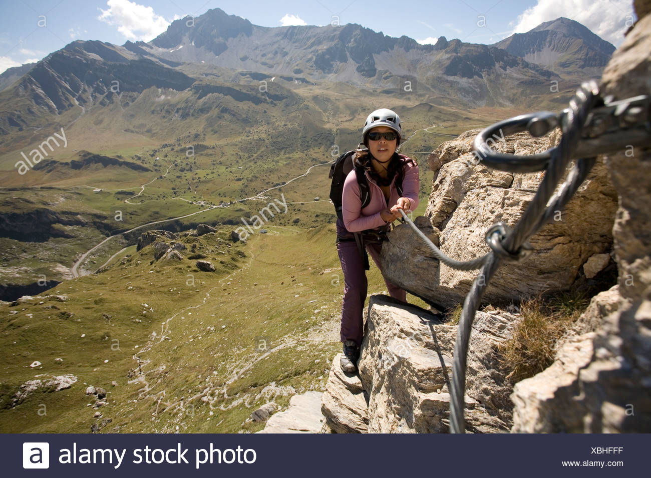 A young woman uses the cable bolted to the rock for climbing support while engaging in the sport of Via Ferrata in the French A - Stock Image