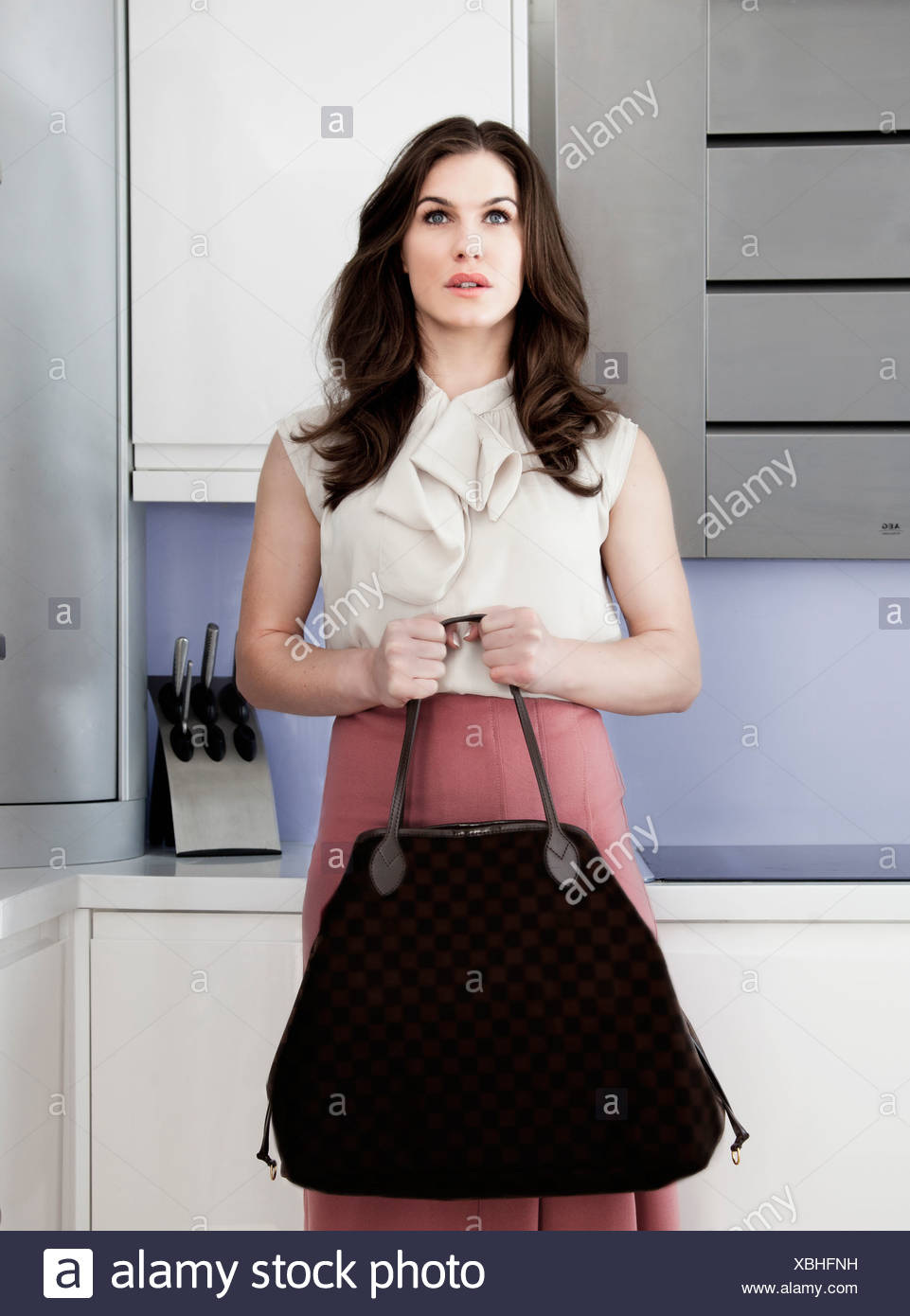 Portrait of young woman holding handbag with blank expression - Stock Image