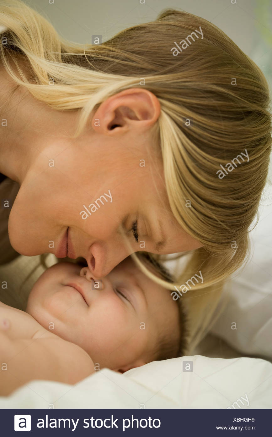 Young mother nuzzling sleeping baby - Stock Image