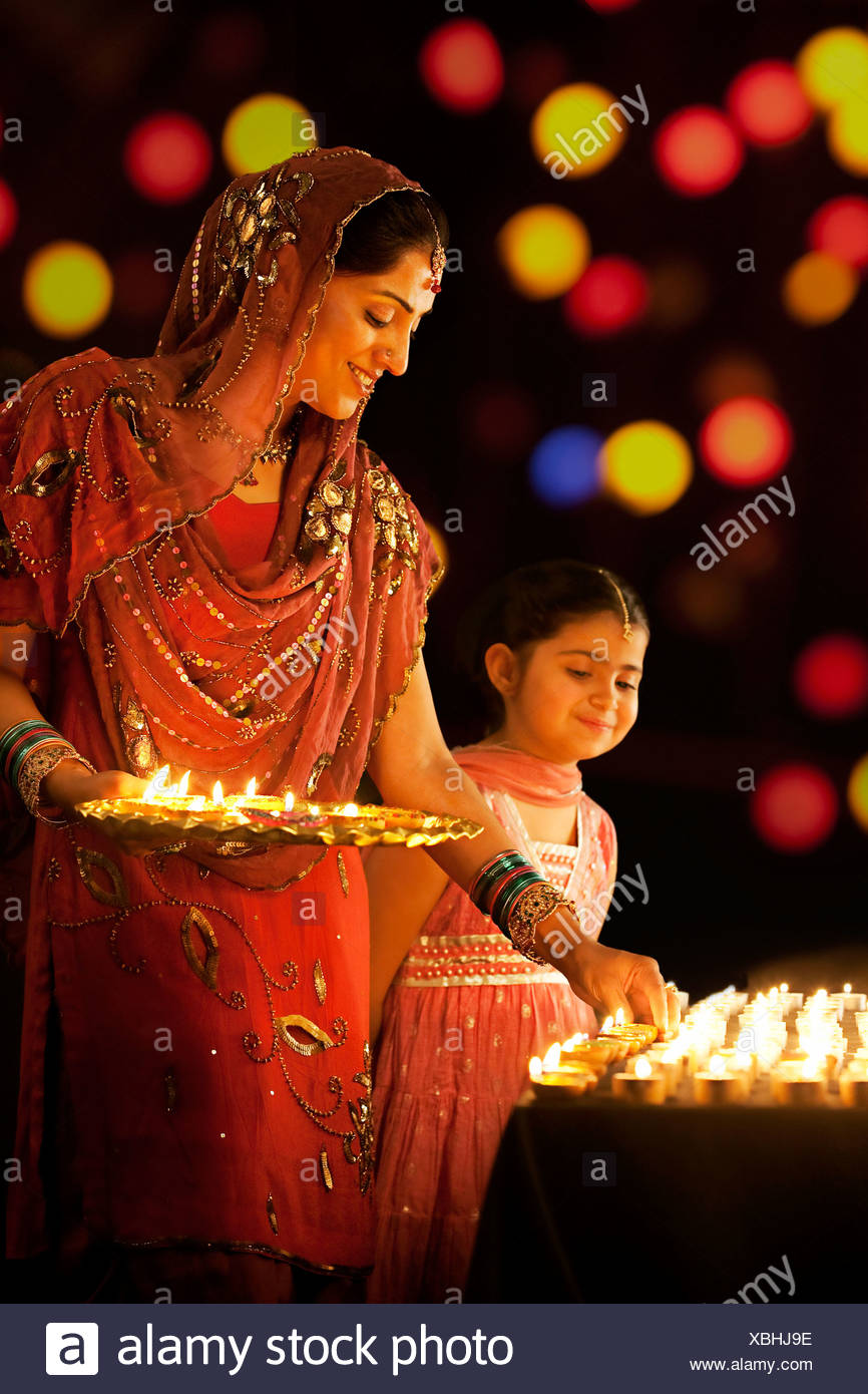 Mother placing diyas on a table while her daughter looks on - Stock Image