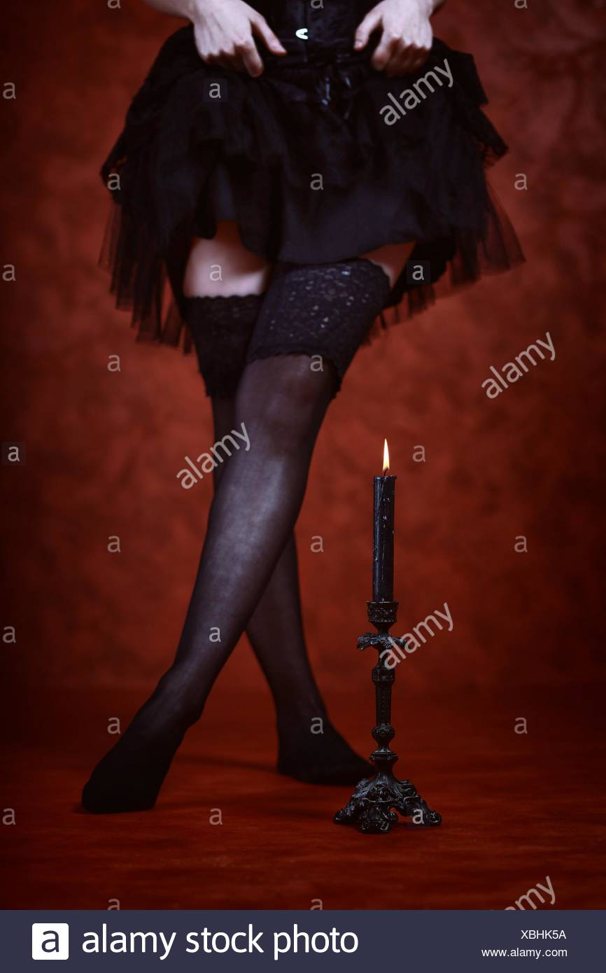 Close up  of a candle, black tights legs in red background - Stock Image
