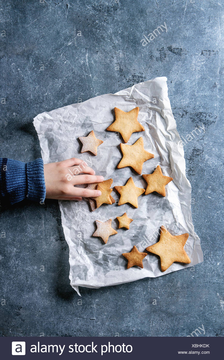 Child's hands in wool pullover take Christmas homemade shortbread star shape sugar cookies different size with sugar powder on baking paper over blue  - Stock Image