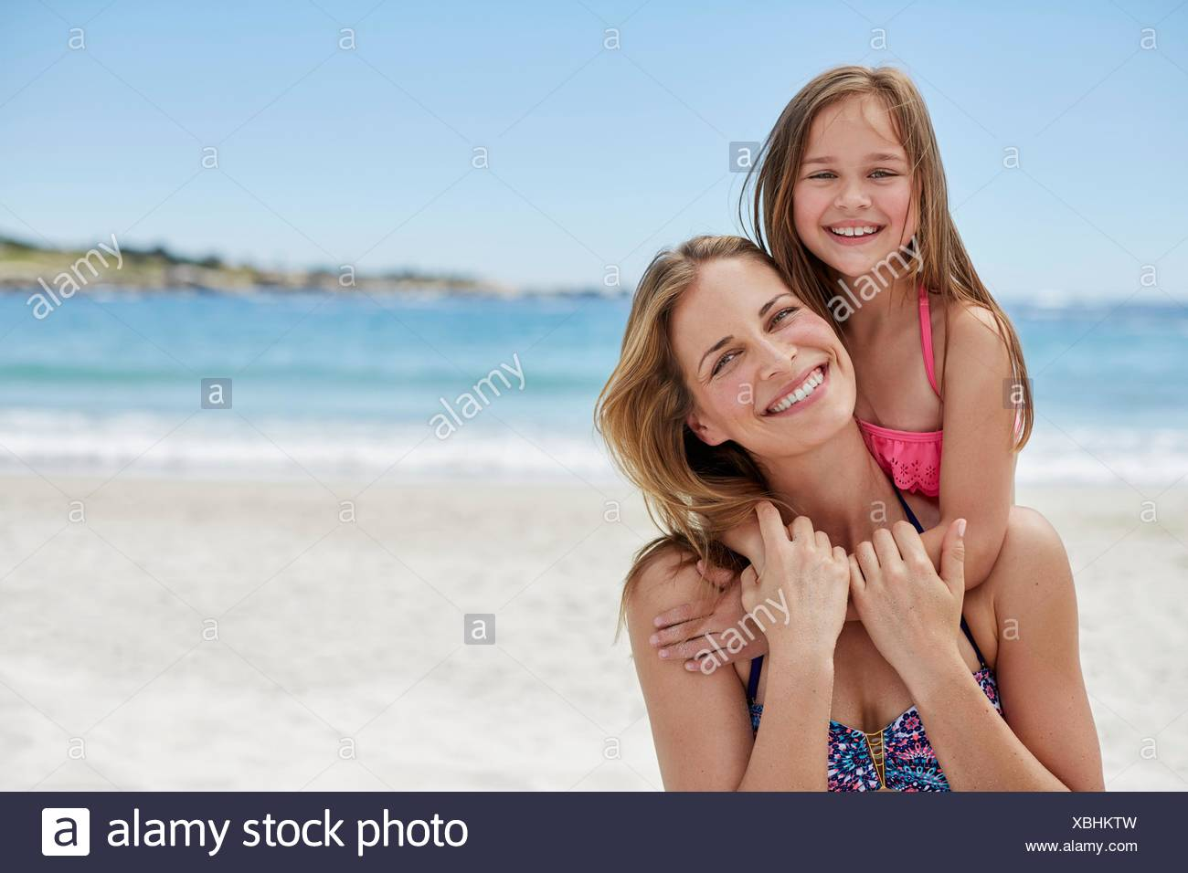 MODEL RELEASED. Mother carrying daughter on her back, portrait. - Stock Image