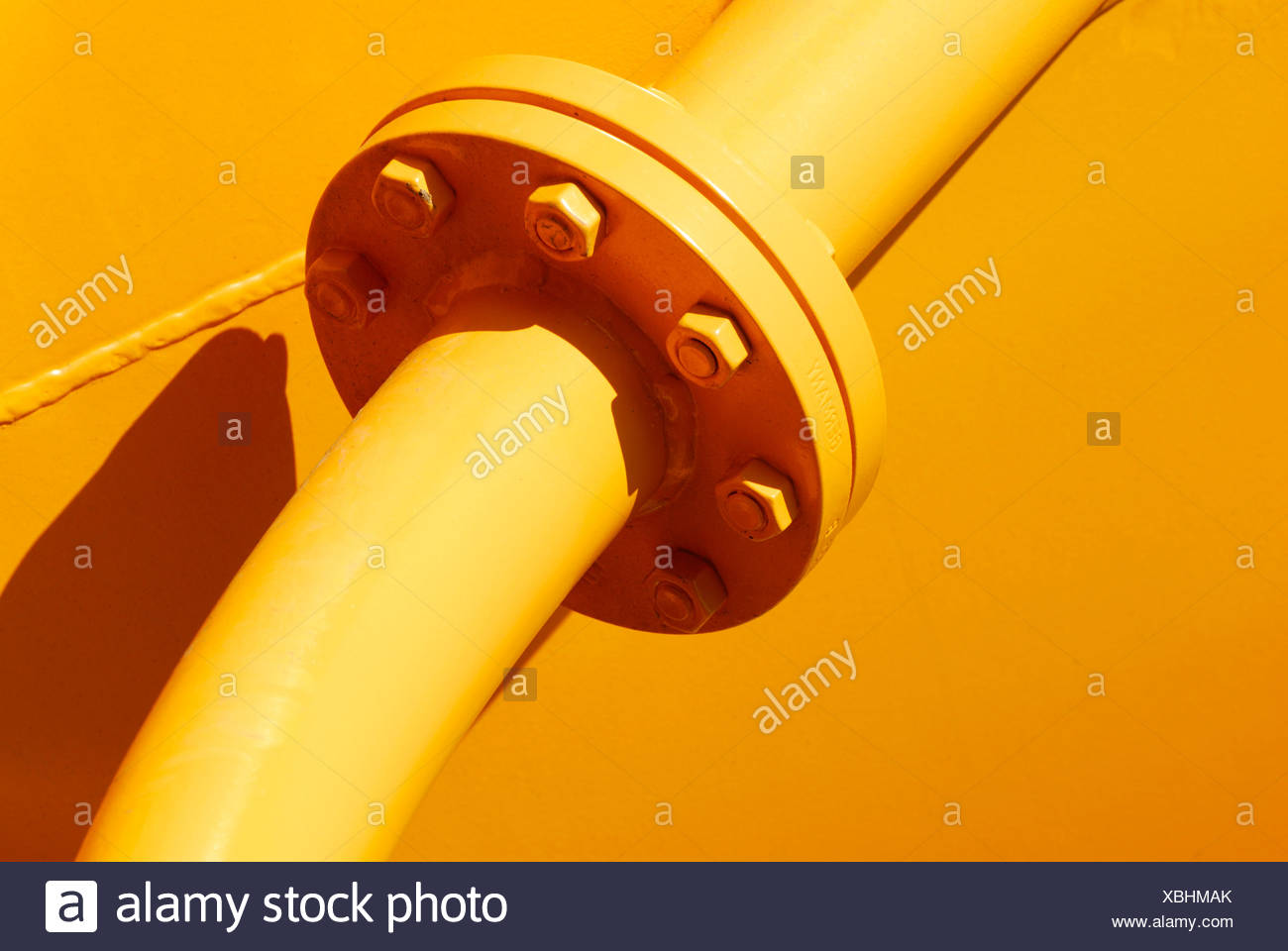 Yellow pipes joined by bolts at a flange, Emmendingen, Baden-Wuerttemberg, Germany - Stock Image