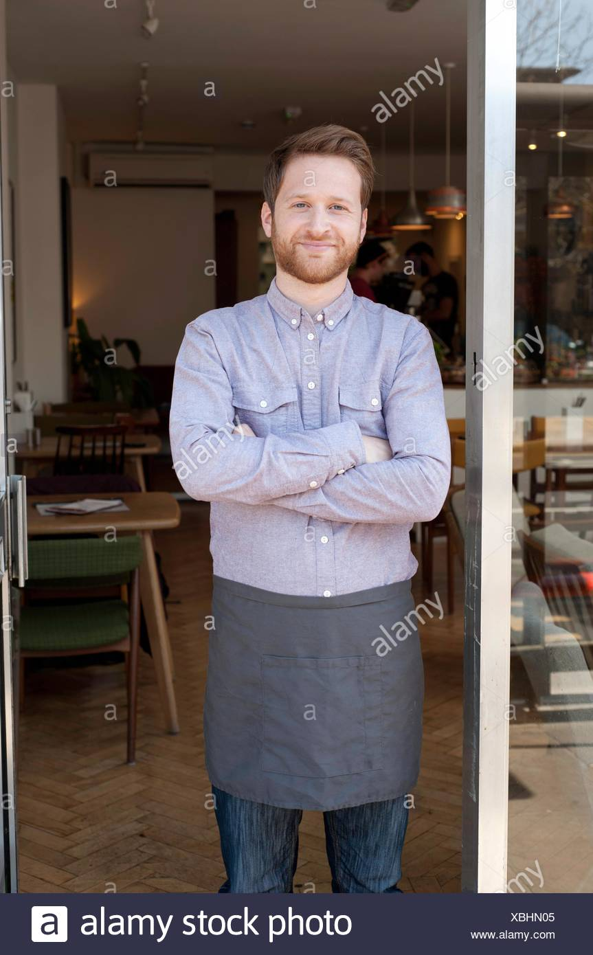 Portrait of proud young male cafe owner in doorway - Stock Image