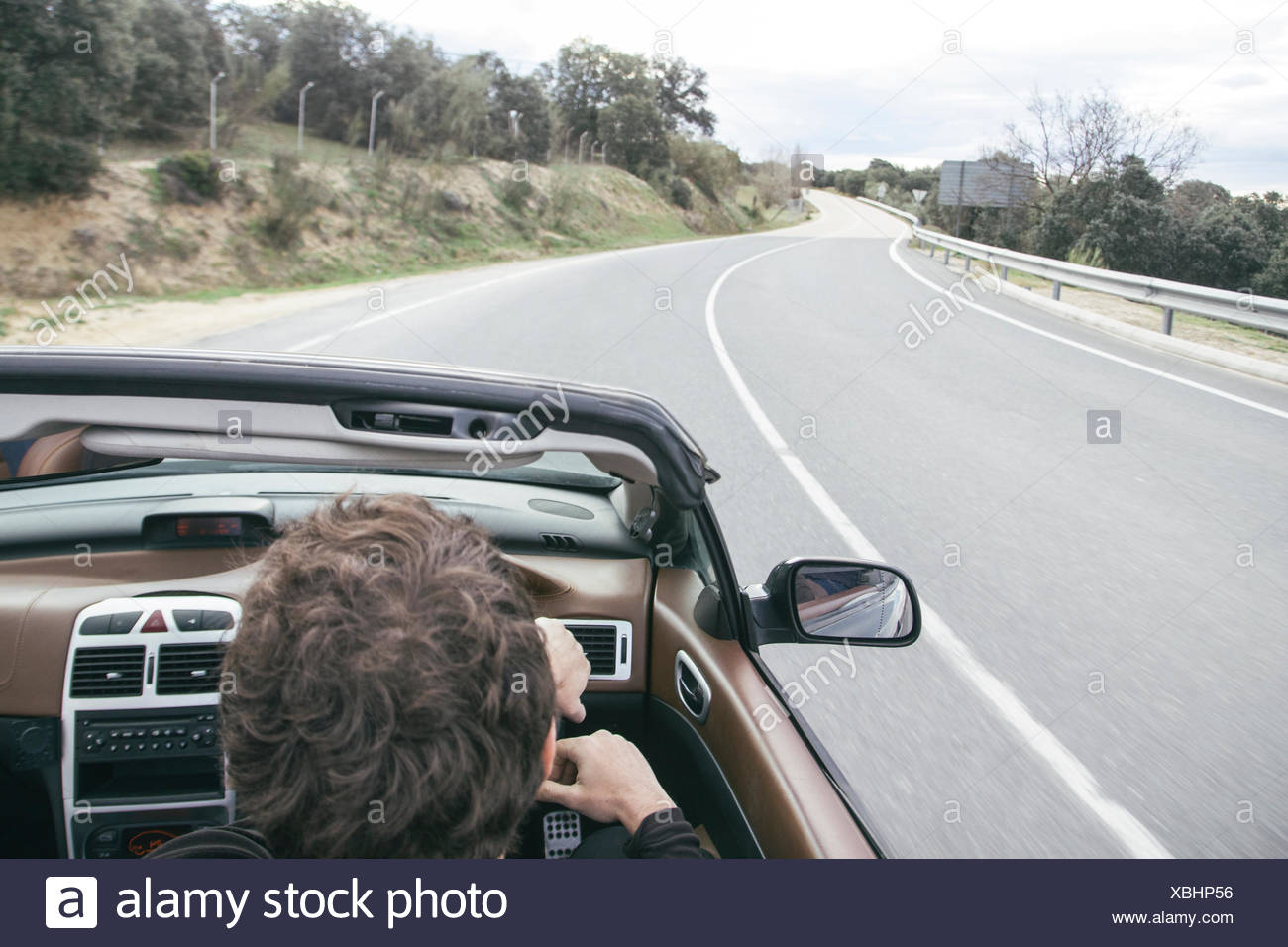 Man driving a convertible car on empty country road - Stock Image