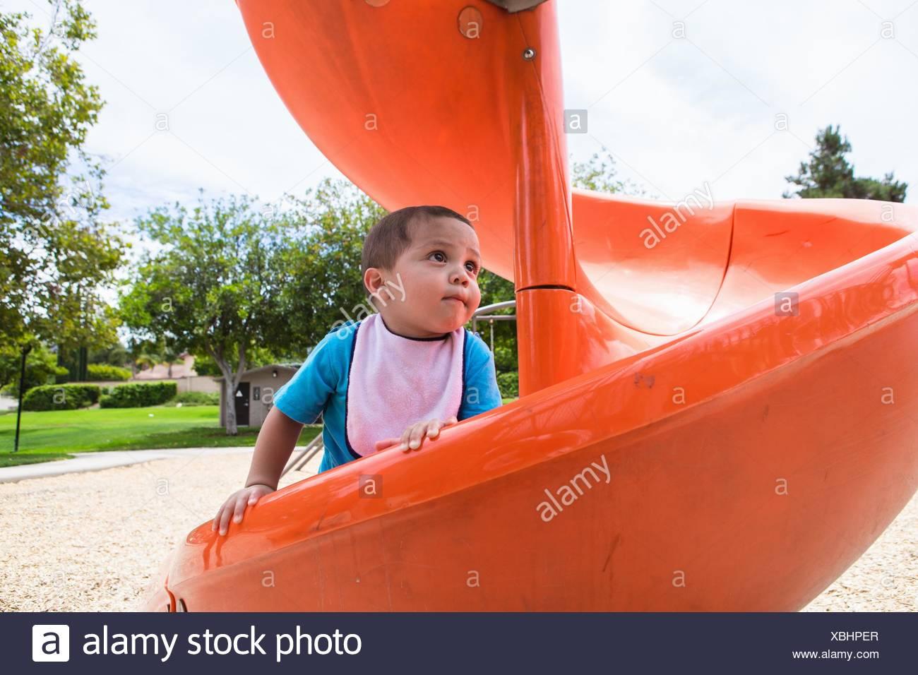 Male toddler climbing up orange playground slide - Stock Image