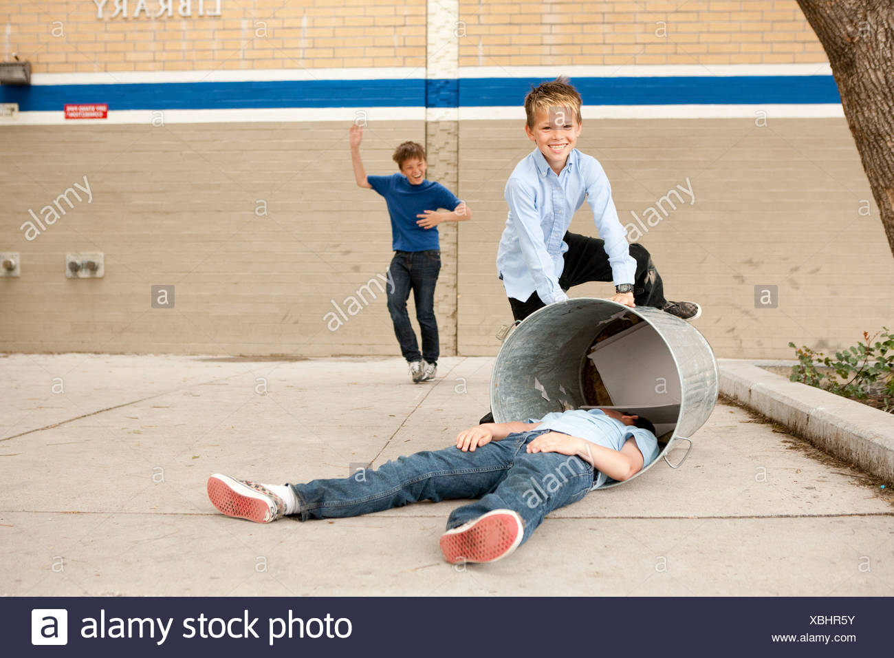 Two boys bullying another, one boy in dustbin - Stock Image