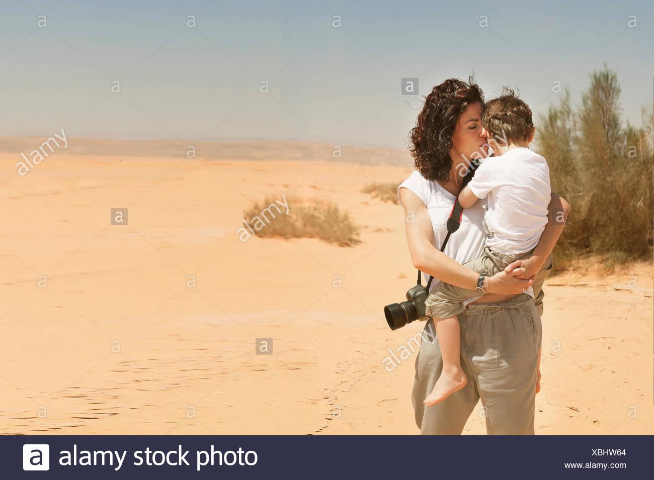 Mother standing in desert carrying her son, Jordan Stock Photo