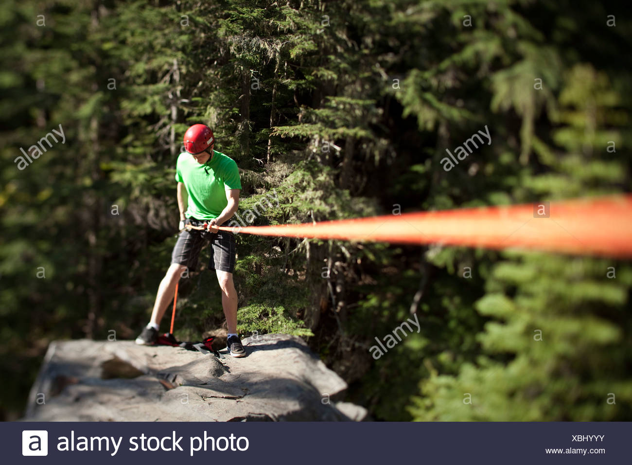 A young man prepares to rappel down a cliff in Idaho. - Stock Image