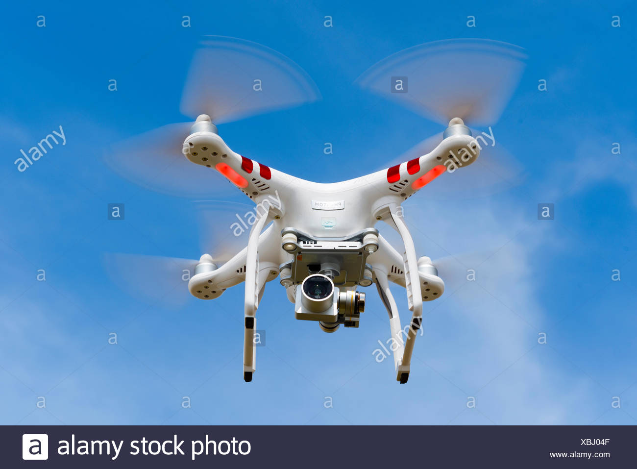 Quadrocopter, drone, with camera flying against a blue sky, DJI Phantom 3 - Stock Image