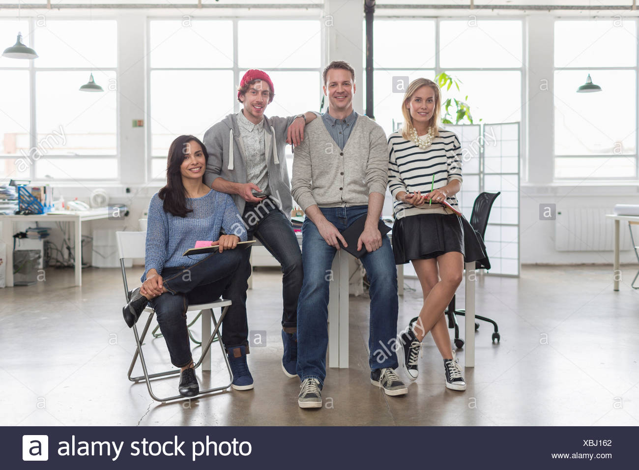 Creative business team sitting together in office, portrait - Stock Image