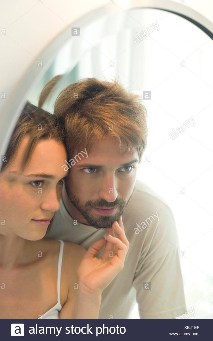 Couple looking into mirror together, wife caressing husand's bearded chin - Stock Image