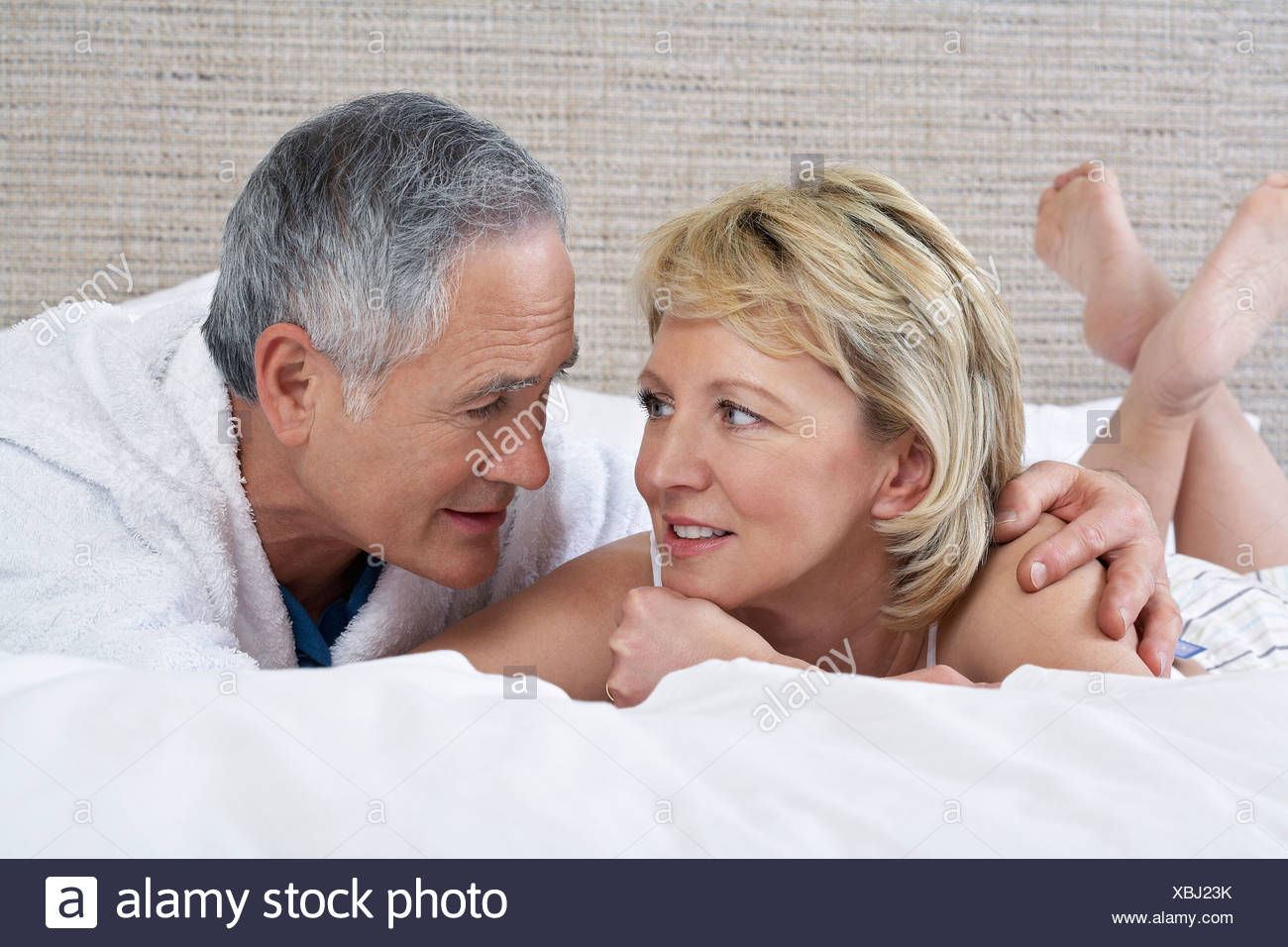 Middle-aged couple lying on bed talking - Stock Image