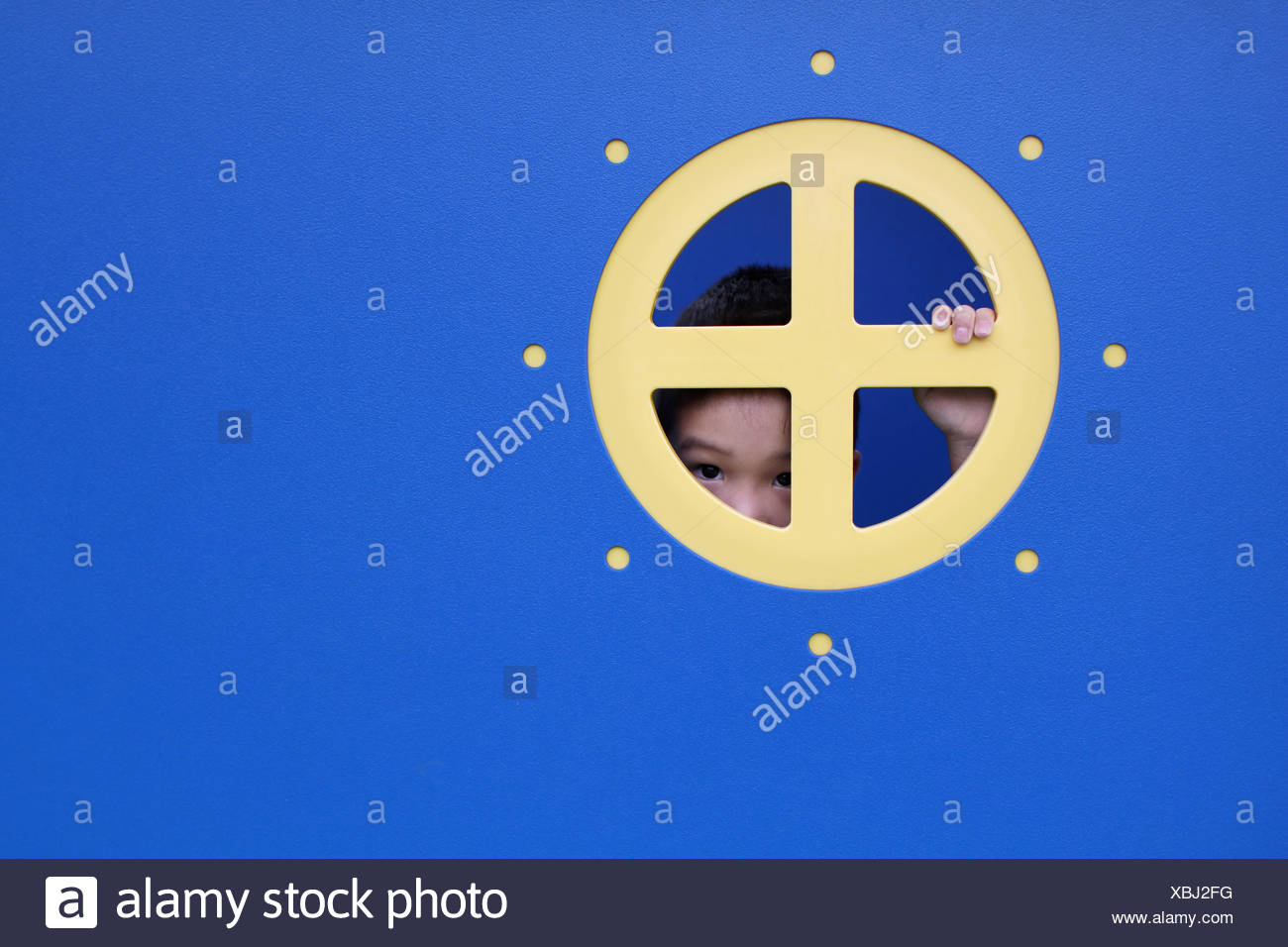 Boy peeking through the round window of a playhouse - Stock Image