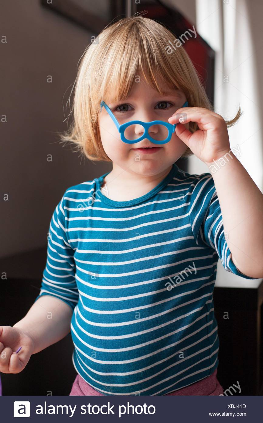 funny portrait of blonde two years old child with striped blue and white sweater inside home playing holding with hand little plastic toy glasses in Stock Photo