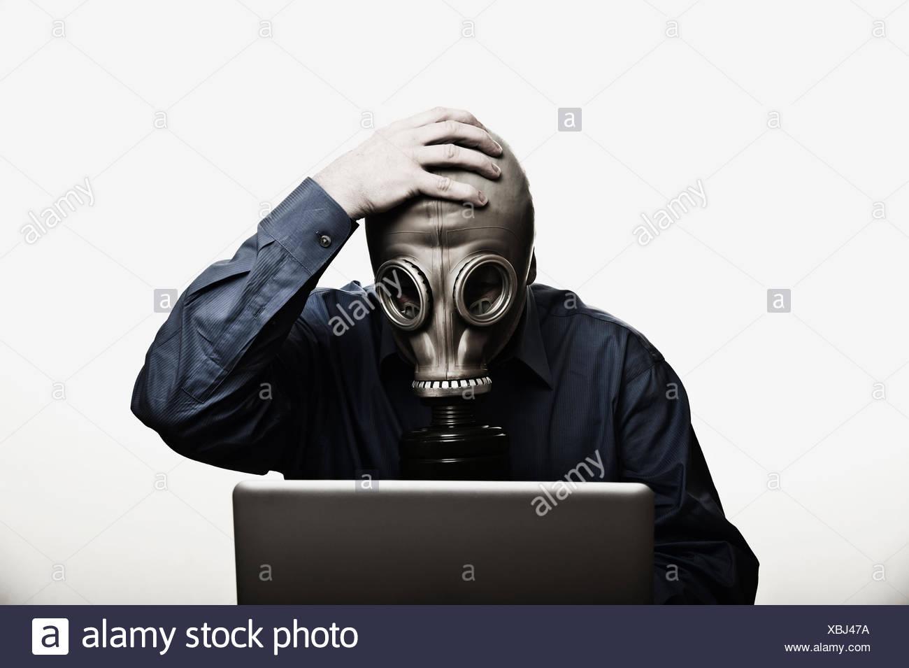 Studio shot of man in front of laptop wearing gas mask - Stock Image