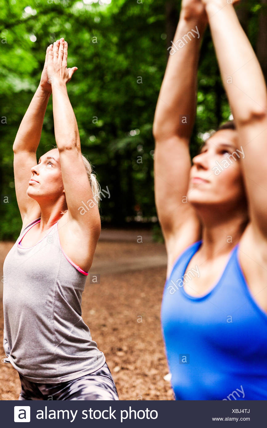 Determined women practicing yoga in tree pose at park - Stock Image