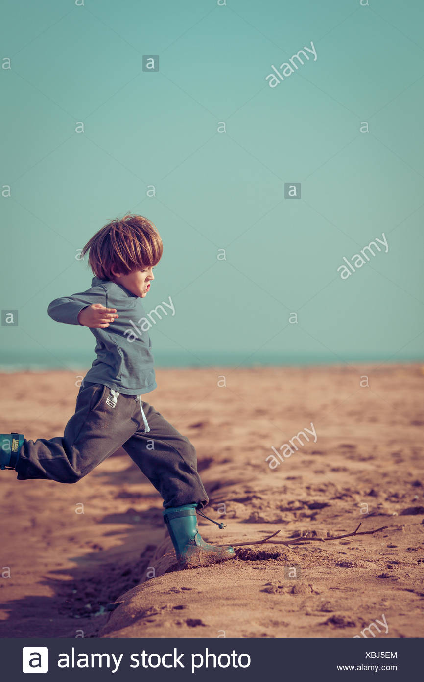 Boy running on beach, Morocco - Stock Image