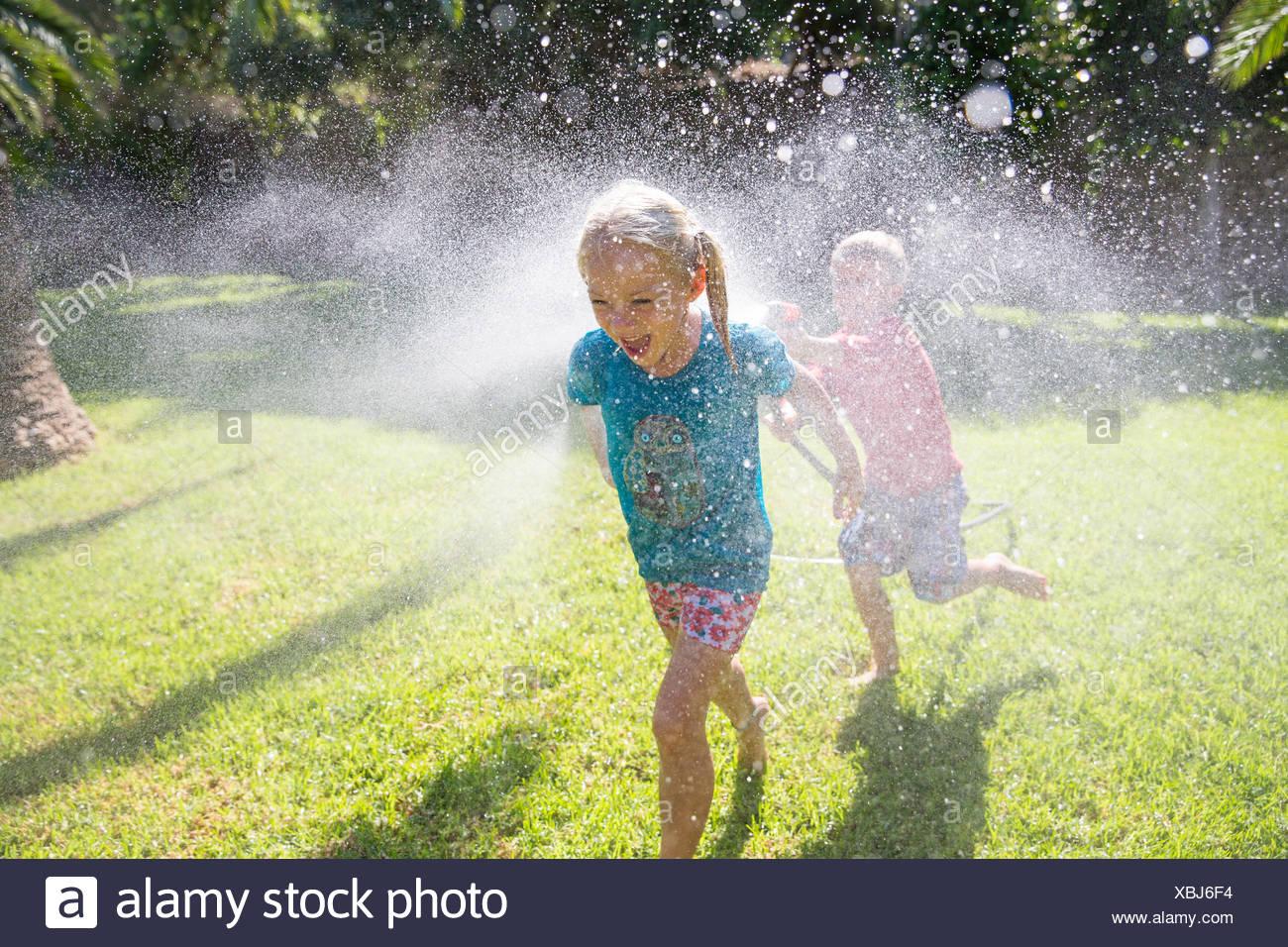 Boy running after girl in garden with water sprinkler - Stock Image