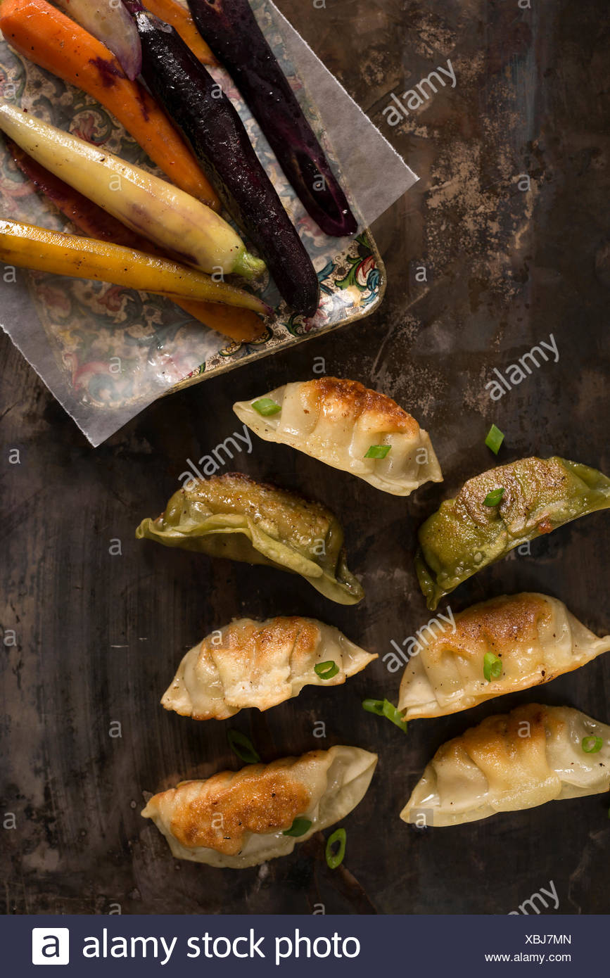 A variety of pot stickers on a rustic metal surface with rainbow carrots. - Stock Image