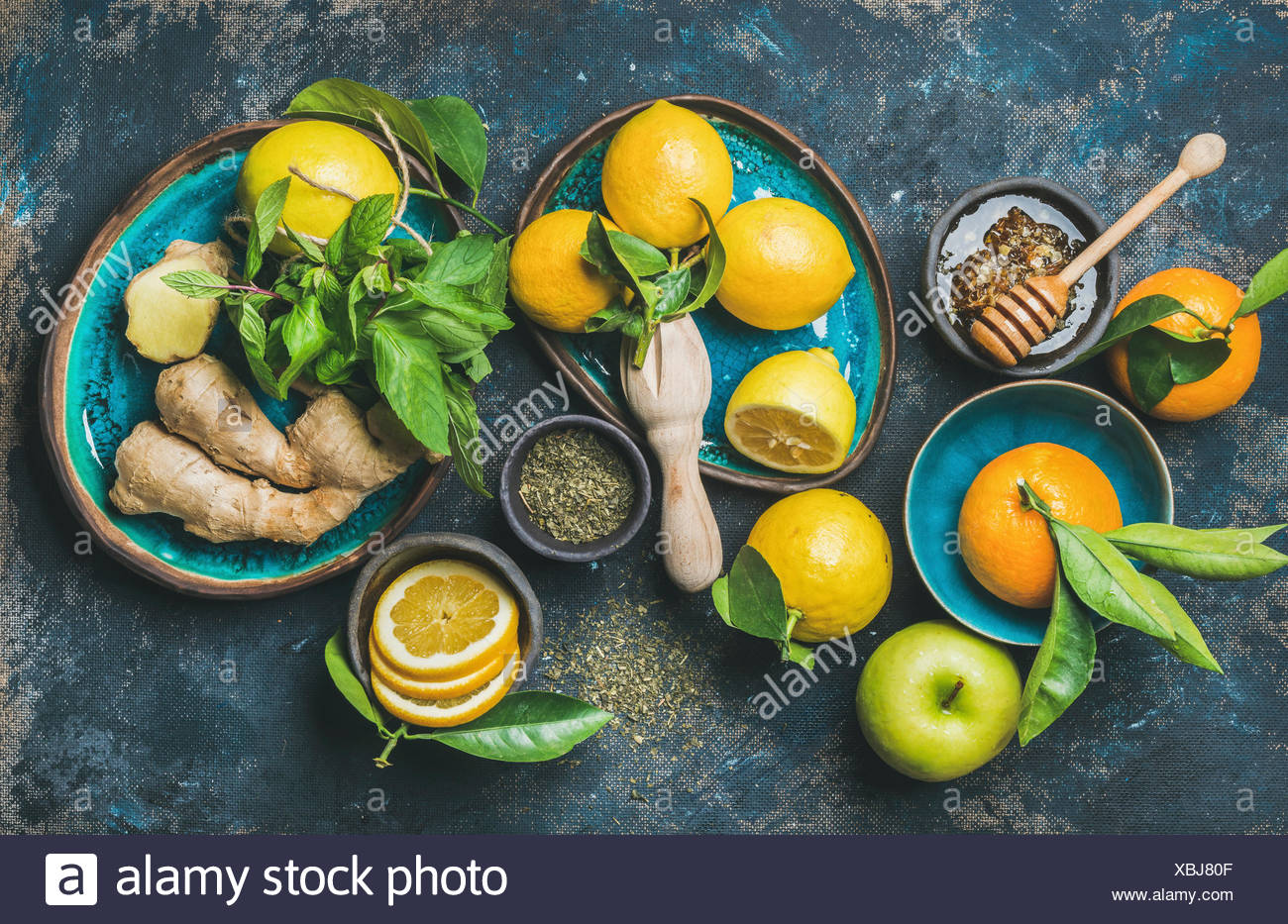 Ingredients for making natural hot drink in blue ceramic plates over dark blue shabby background, top view. Oranges, mint, lemon, ginger, honey and ap - Stock Image