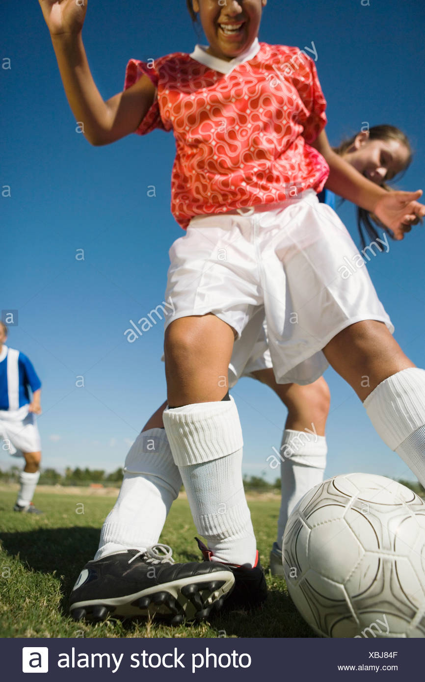 Girls (13-17) playing soccer, one tackling another, low angle view, cropped - Stock Image