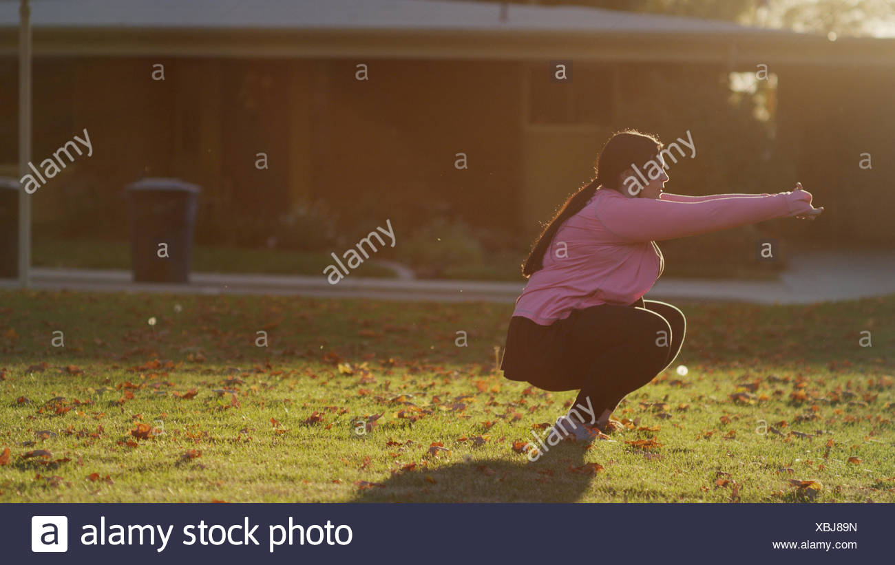 Profile of backlit woman squatting and working out in sunny backyard - Stock Image