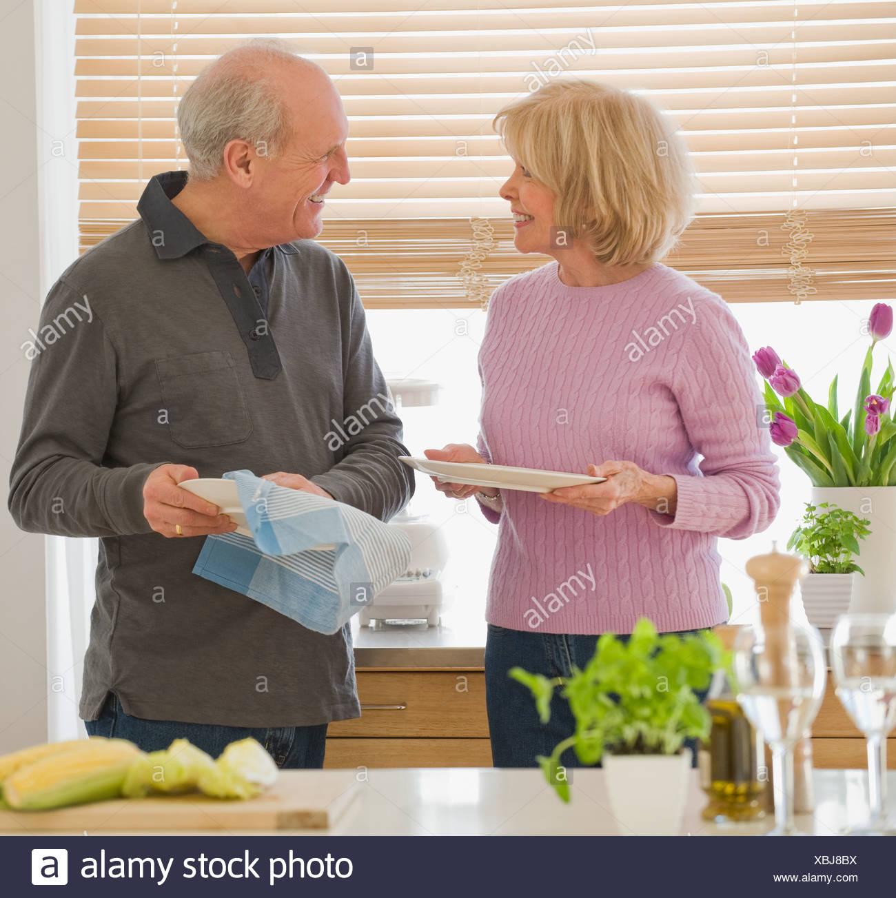 Senior couple drying dishes - Stock Image