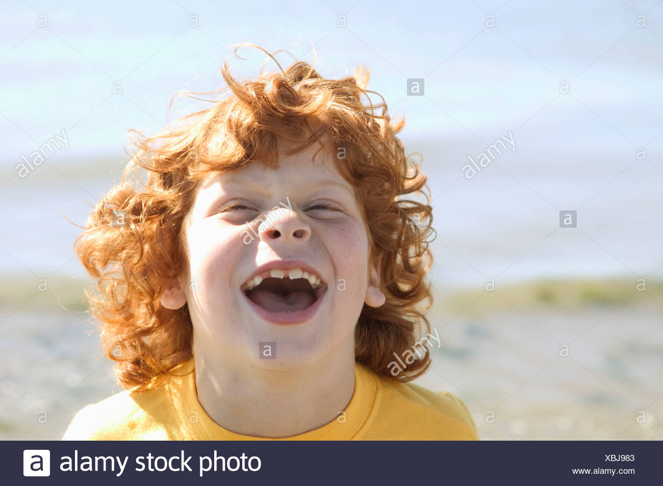 Portrait of a laughing red headed boy - Stock Image