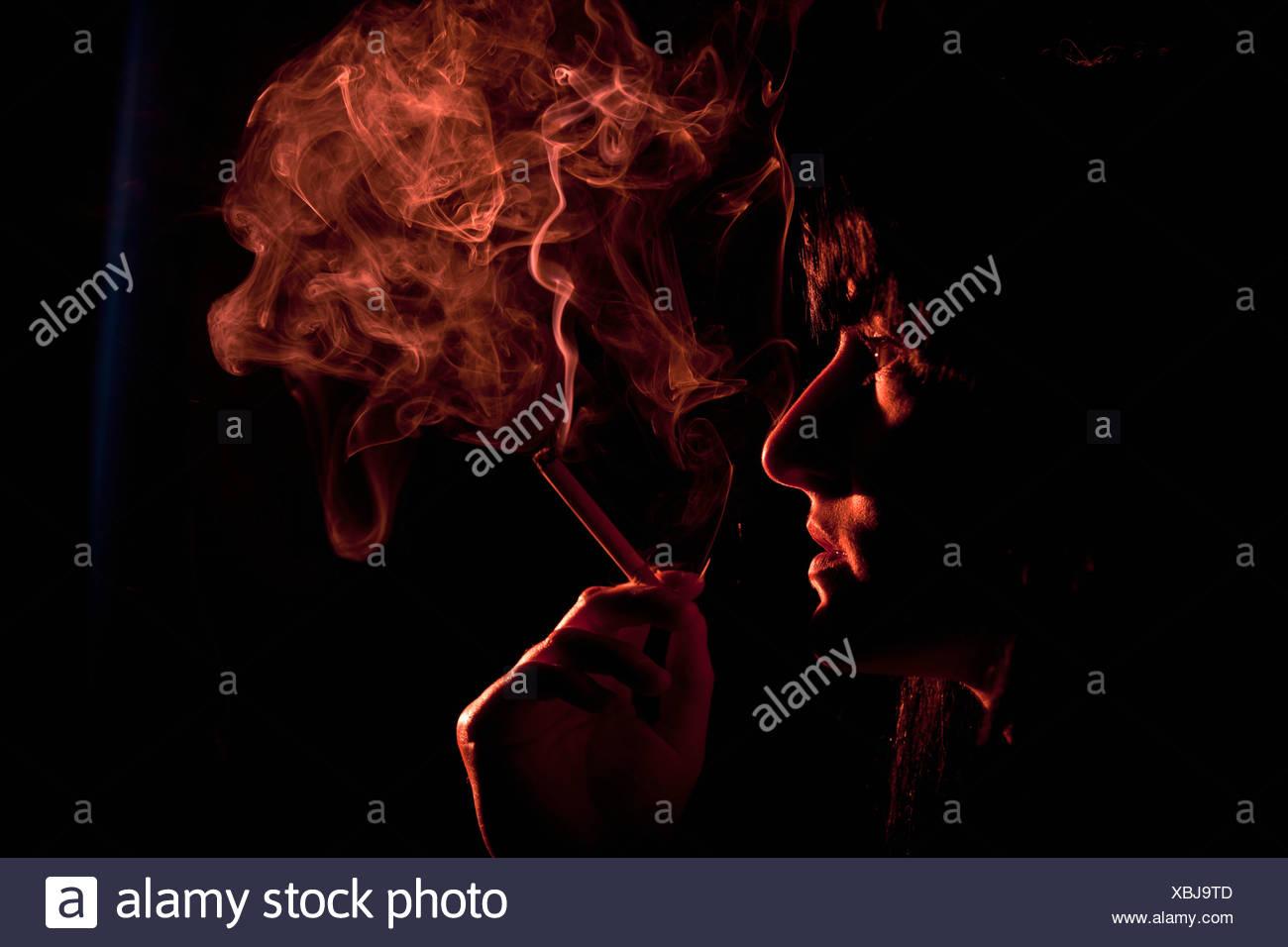 Illuminated profile of woman smoking - Stock Image
