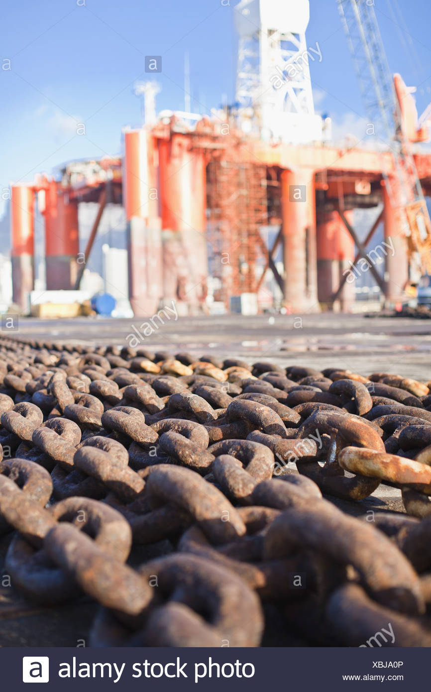 Rusted chains on oil rig - Stock Image