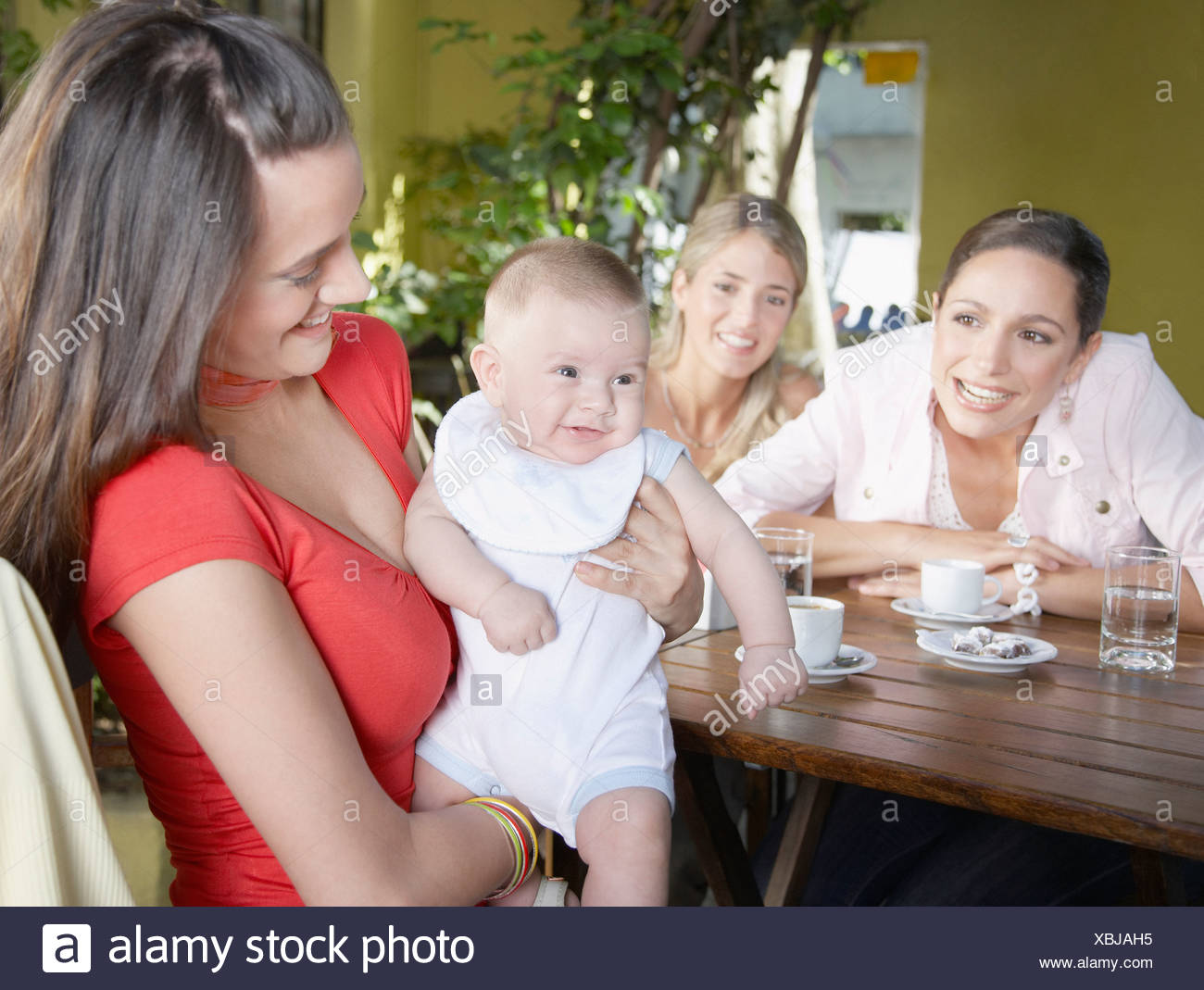 Three women on outdoor patio where one is holding a smiling baby - Stock Image